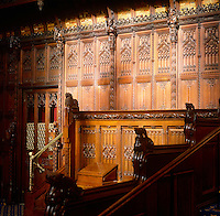 A corner of the Chamber, showing carved panelling, heads of kings and painted coats of arms