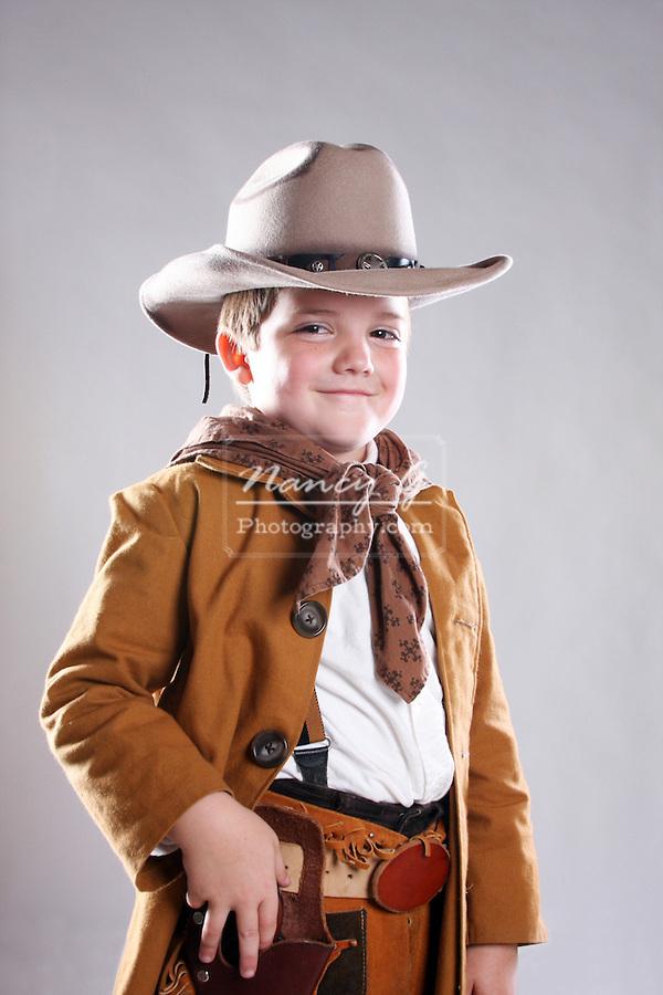 A young cowboy child reaching for his fake gun