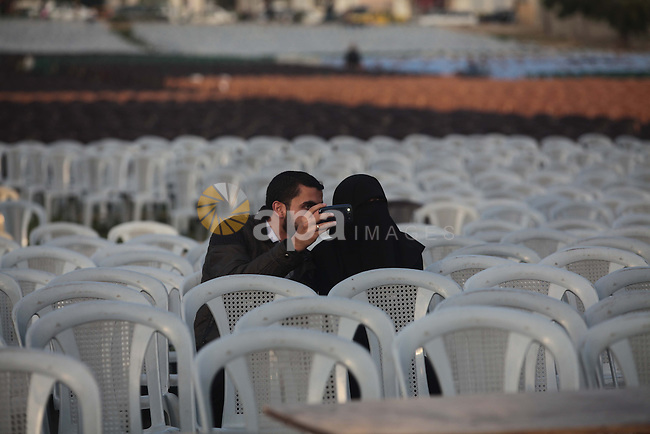 A Palestinian man takes pictures for the placard depicting late Hamas leaders, during the preparation of the Hamas festival in Gaza City, March 22, 2014. Hamas organized a festival in the anniversary of the death of Hamas leaders Sheikh Ahmed Yassin, Ibrahim Makadmeh, and Abdul Aziz Rantisi. Photo by Ashraf Amra