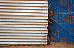 A girl looks out from her family's shelter in Bunj, a town in Maban County, South Sudan. Maban is host to four refugee camps that together shelter more than 130,000 refugees from the Blue Nile region of Sudan. Jesuit Refugee Service, with support from Misean Cara, provides educational and psycho-social services to both refugees in the camps and the host community.