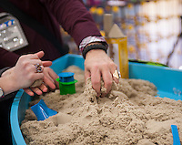 Visitors play with Kinetic Sand from WABU Fun at the 111th American International Toy Fair in the Jacob Javits Convention center in New York on Monday, February 17, 2014. WABU Fun announced that they will be building the World's Tallest Toy at the National Building Museum in the Fall using their Superstructs construction toy.  (© Richard B. Levine)