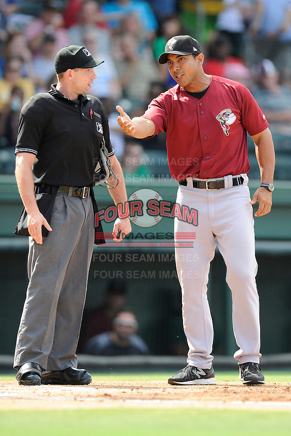 Manager Luis Rojas (19) of the Savannah Sand Gnats argues a call with home plate umpire George Reidel during a game against the Greenville Drive on Sunday, August 24, 2014, at Fluor Field at the West End in Greenville, South Carolina. Greenville won, 8-5. (Tom Priddy/Four Seam Images)