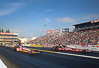 Feb 9, 2014; Pomona, CA, USA; NHRA top fuel dragster driver Doug Kalitta (left) races alongside Spencer Massey during the Winternationals at Auto Club Raceway at Pomona. Mandatory Credit: Mark J. Rebilas-