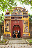 VIETNAM, Hue, a woman stands with her husband and brother in law by a large painted gate inside the Citadel