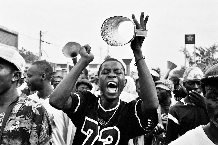 Haitian man playing a home made drum during a pro-Preval demonstration coming from Cite Soleil on the day of the elections. After waiting over four hours for the voting stations to open the local residents took to the streets.