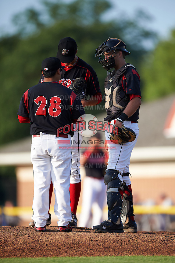 Batavia Muckdogs pitching coach Brendan Sagara (28) talks with pitcher Jordan Holloway (56) and catcher Blake Anderson (26) during a game against the Auburn Doubledays July 10, 2015 at Dwyer Stadium in Batavia, New York.  Auburn defeated Batavia 13-1.  (Mike Janes/Four Seam Images)