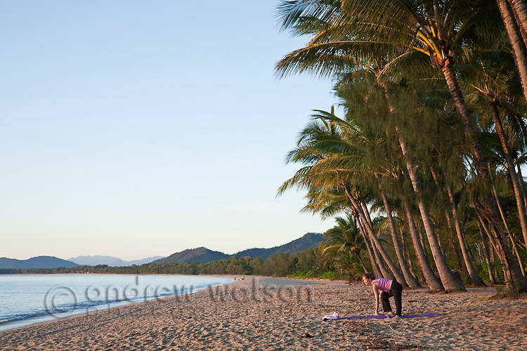 Woman doing yoga on beach at Palm Cove, Cairns, Queensland, Australia