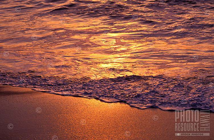 Close up of water washing ashore a North Shore beach lit by the sunset