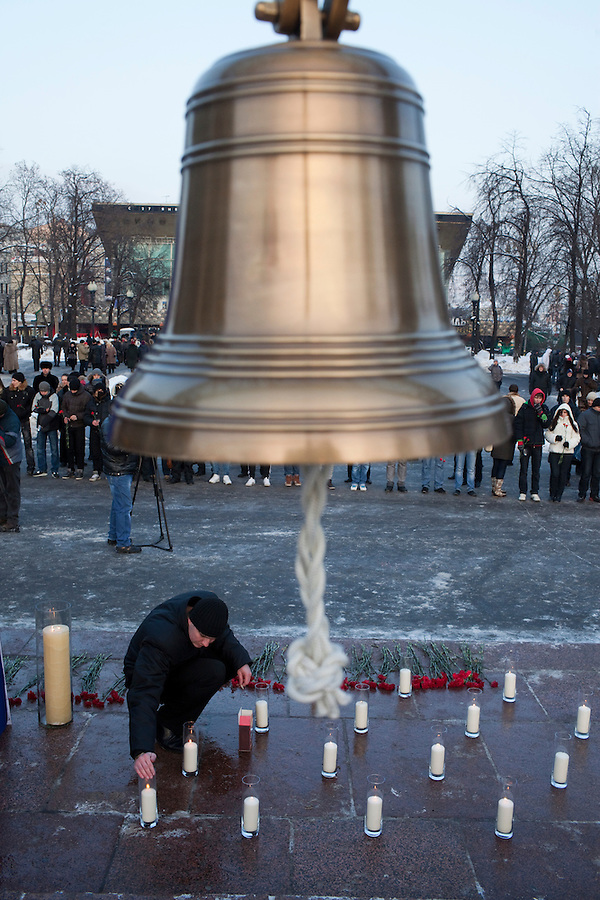 Moscow, Russia, 27/01/2011..A man lights candles at a memorial ceremony in central Moscow for the 35 people killed in the Domodedovo airport bombing.