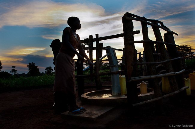 Ogobi village...Emily, 16,  pumps 2 cans of water at dusk for her family and doesn't have to walk too far now with the new well, about 10 minutes.
