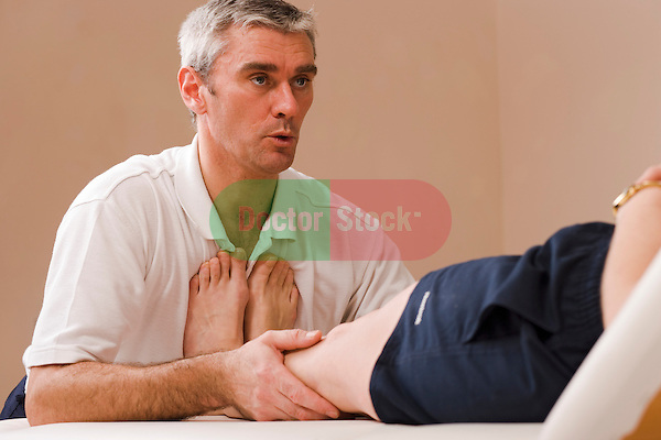 physiotherapist manipulates womans legs