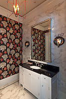Formal Powder Bath has a pop of coral with the chandelier that leads your eye to<br /> the wallpaper.