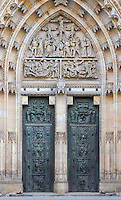 The central gate of the Main Portal or hlavni portal of St Vitus Cathedral, with crucifixion high relief above in the Gothic arch, and double bronze gates below with scenes of the building of the cathedral from 925-1929, St Vitus cathedral, a Gothic Roman catholic cathedral founded 1344, within Prague Castle, Prague, Czech Republic. The relief work was completed by O Spaniel according to the plans of V H Brunner. The cathedral's full name is the St Vitus, St Wenceslas and St Adalbert cathedral and is the largest church in the Czech Republic. The historic centre of Prague was declared a UNESCO World Heritage Site in 1992. Picture by Manuel Cohen