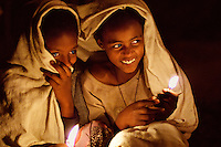 Girls waiting in the predawn of the Timkat festival in Lalibela, Ethiopia 2006.<br /> Two girls giggle conspiratorially in the early predawn hours of the Orthodox Christian Timkat festival. On this particular day of week long rituals and festivities the crowds gather to await being sprinkled with the blessed waters from the reinactment of the baptism of Jesus in the Jordan River.