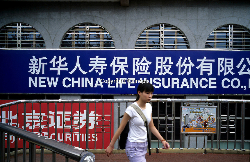 A girl walks past the building of  New China Life Insurance in Beijing, China. 07-28-2005 (Lou Linwei/Sinopix)