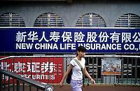 A girl walks past the building of  New China Life Insurance in Beijing, China. 07-28-2005 (Lou Linwei/Sinopix)