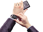 Hands of a person wearing Samsung Galaxy Gear watch and holding a smartphone isolated on white background