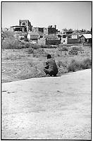 Uzbekistan - Chilangu - Man sitting in front of Hakkim Mullo Mir Khanagha cemetery.