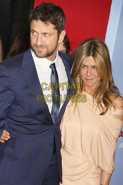 GERARD BUTLER & JENNIFER ANISTON .'The Bounty Hunter' New York Premiere held at the Ziegfeld Theatre, New York , NY, USA, 16th March 2010..arrivals half length navy blue tie suit white shirt beige grecian jersey dress off the cut out shoulder arm around beard facial hair .CAP/ADM/AC.©Alex Cole/AdMedia/Capital Pictures.