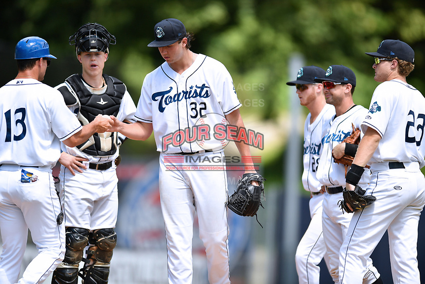 Asheville Tourists manager Warren Schaeffer (13) takes the ball from starting pitcher Riley Pint (32) as catcher Brian Serven (25), shortstop Taylor Snyder (28), second baseman Max George (3) and first baseman Tyler Nevin (23) look on during a game against the Rome Braves at McCormick Field on July 30, 2017 in Asheville, North Carolina. The Braves defeated the Tourists 7-3. (Tony Farlow/Four Seam Images)