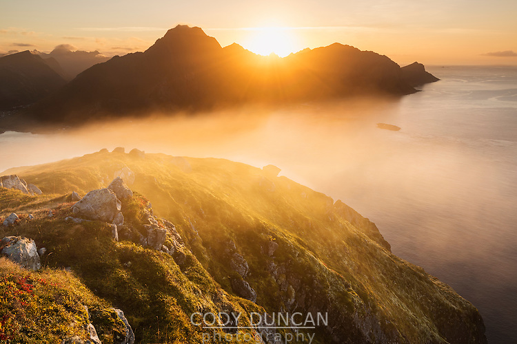 Sunset behind mountains from summit of Offersoykammen, Vestvagoya, Lofoten Islands, Norway