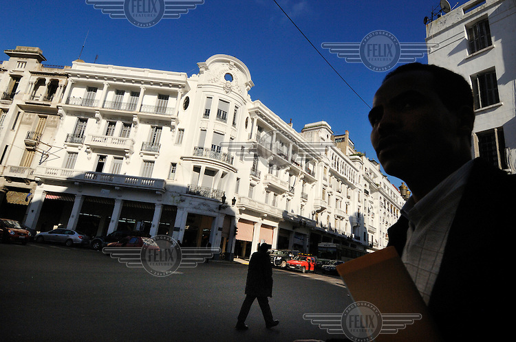 People walk past the grand Art Deco buildings that line Boulevard Mohammed V in Casablanca's French colonial era New Town.