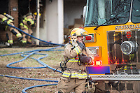 STAFF PHOTO ANTHONY REYES &bull; @NWATONYR<br /> Jason Cooley, Springdale firefighter, carries a dog away from a house fire Wednesday, Dec. 24, 2014 at 1503 Thrush Street in Springdale. Cooley, called the Dog Whisperer by his co-workers, found the dog hiding in the corner of the yard of a duplex fire. There were no injuries in the fire which the owner thinks started near his space heater. The duplex owned by Marc Miller lived in the damaged unit. Firefighter got the call for the blaze at 12:30 p.m. and the fire was under control within 20 minutes. Four dogs were in the building, three are safe and one was missing as of press time.