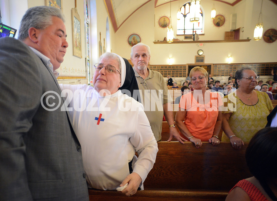 BRISTOL, PA - MAY 31:  Ralph DiGuiseppe of Bristol, Pennsylvania is hugged by Sister Mary Donald, O. SS. T after the closing of St. Ann's parish is announced May 31, 2014 in Bristol, Pennsylvania. (Photo by William Thomas Cain/Cain Images)