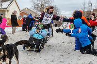 Ryne Olson runs down Cordova Street giving high-fives to spectators during the Ceremonial Start of the 2016 Iditarod in Anchorage, Alaska.  March 05, 2016