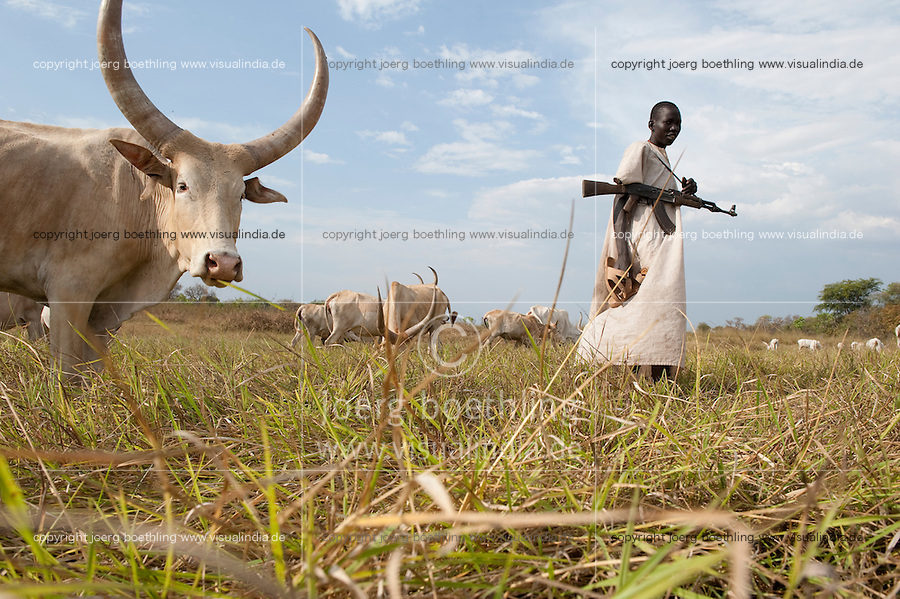 SOUTH SUDAN, Rumbek, young Dinka man protect the Zebu cattle of his family with AK-47 rifle against Nuer cattle raider / SUED SUDAN Rumbek , Matur ein 18 jaehriger Dinka Hirte schuetzt Zeburinder vor Viehdiebstaehlen durch Nuer mit seinem Kalaschnikov Maschinengewehr