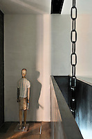 A functional space with concrete walls and a wood floor. A steel chain hangs down from the ceiling. A figurine stands in the corner.
