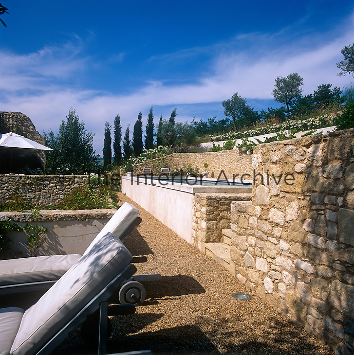 An outdoor lap pool set in a stone surround and sun-loungers are set out on a gravel terrace.