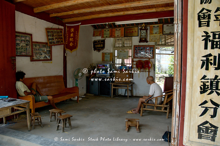 Two men watching television inside their home, Fuli Village, Guangxi, China.