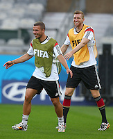 Arsenal duo Lukas Podolski and Per Mertesacker of Germany share a joke during training ahead of tomorrow's semi final vs Brazil