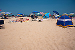Sun worshippers nap among scattered umbrellas and beach shelters on a summer day at Rehoboth Beach, Delaware, USA.