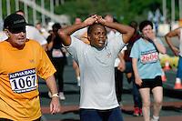 02 NOV 2003 - ATHENS, GREECE - A competitor reaches the Athens Classic Mini Marathon finish line. (PHOTO (C) NIGEL FARROW)
