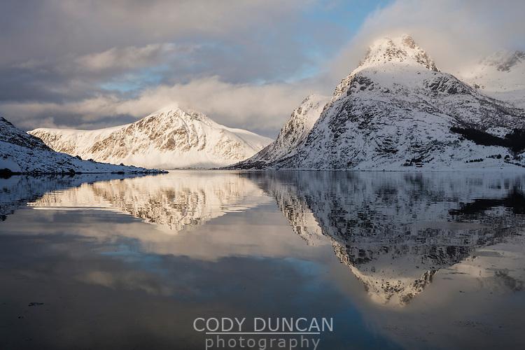 Winter mountain reflections in calm water of Flakstadpollen, Flakstadøy, Lofoten Islands, Norway