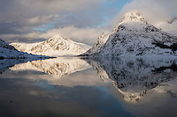 Winter mountain reflections in calm water of Flakstadpollen, Flakstadøy, Lofoten Islands, Norway