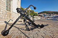 A traditional black anchor at the port of Hydra, Greece