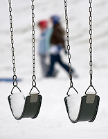 Snow covers the seats on a swing as children and adult sled a small hill in a city park in Westerville, Ohio, after the first snowfall of the season.  Photo Copyright Gary Gardiner. Not for reproduction without written permission.