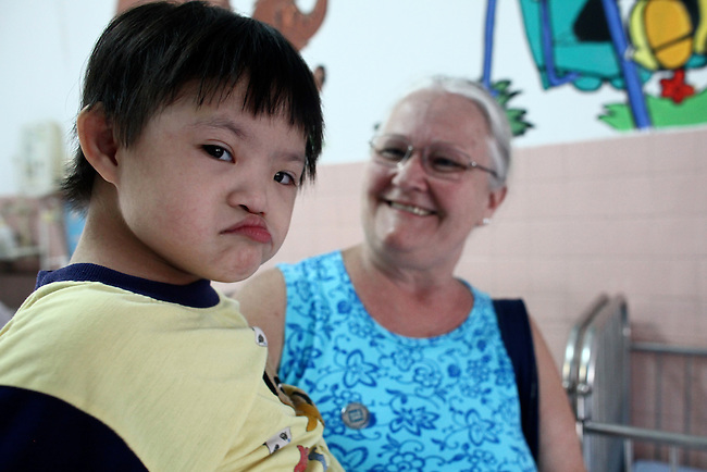 Signe Nelson, a member of Veterans for Peace, sits with a young Agent Orange victim in the Agent Orange children's ward of Tu Du Hospital in Ho Chi Minh City, Vietnam.  About 500 of the 60,000 children delivered each year at the maternity hospital, Vietnam's largest, are born with deformities, according to doctors. May 1, 2013.