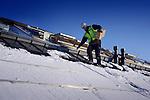 Doorwerken tijdens een koude vorstperiode op een bouwplaats in de winter kan gevaarlijk zijn op een glad ondersneeuwd bevroren dak. COPYRIGHT TON BORSBOOM