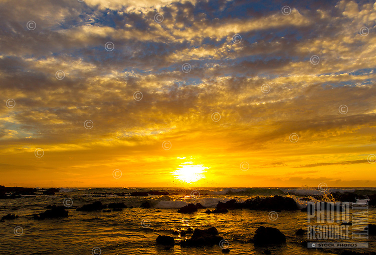 The splashing water reflects a vibrant, orange Puako sunset on the Big Island.