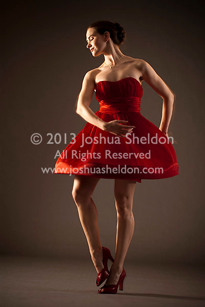 Young woman dancing in red dress with motion