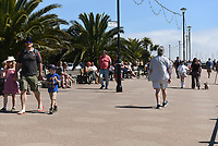 Members of the public enjoy the warm weather on the promenade in Torquay during the COVID-19 pandemic and lockdown