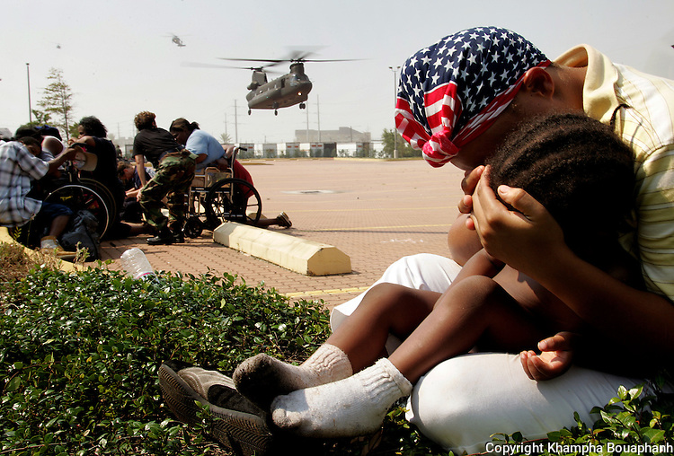 A mom covers her son as a Chinook helicopter land to evacuate people from the Ernest N. Morial Convention Center in downtown New Orleans on Saturday, September 3, 2005.  Thousands took refuge at the convention center after Hurricane Katrina devasted the city.  (photo by Khampha Bouaphanh)