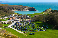 BNPS.co.uk (01202 558833)<br /> Pic: Graham Hunt/BNPS<br /> <br /> The car park a Lulworth Cove in Dorset was nearly full over weekend<br /> <br /> A holiday park close to one of the most popular beauty spots in the country has been slammed for flouting government advice on coronavirus.<br /> <br /> Durdle Door Holiday Park in Dorset sits in the shadow of the limestone arch within the grounds of the picturesque Lulworth Estate.<br /> <br /> Despite stark warnings to avoid all social contact, the park has decided to remain open and was even touting for business online yesterday.<br /> <br /> The car parks around the Lulworth estate have also been crammed full over the weekend despite pleas from experts for people to stay in their homes.