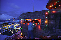 David Hart owner of a cell phone company in Dutch Harbor puts up Christmas lights around an old WWII bunker in December 1993.