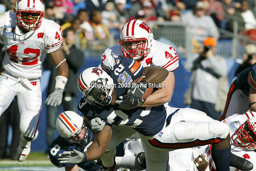 Nashville, Tennessee - 12/31/03. University of Wisconsin linebacker Kyle McCorison (43) tackles Auburn University running back Ronnie Brown (23) at the Gaylord Hotels Music City Bowl. Auburn beat Wisconsin 28-14 at The Coliseum. (Photo by David Stluka)