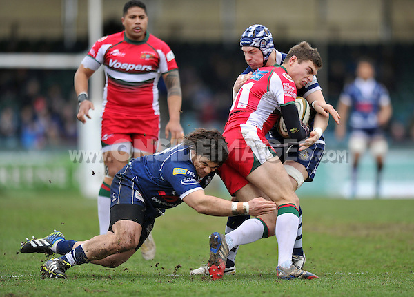 Chris Elder is double-tackled by Mitch Eadie and Gaston Cortes. Greene King IPA Championship match, between Bristol Rugby and Plymouth Albion on February 23, 2014 at the Memorial Stadium in Bristol, England. Photo by: Patrick Khachfe / JMP